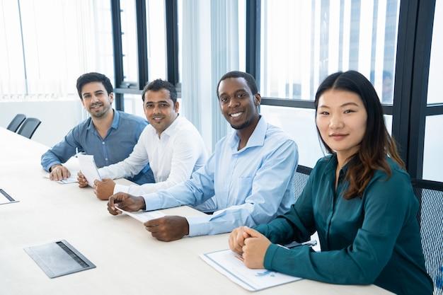 Glimlachende multi-etnische managers die met grafieken in raadsruimte werken.