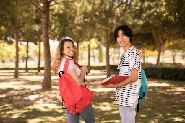 Glimlachende multi-etnische tienervrienden die over schouder kijken