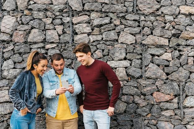 Glimlachende multi-etnische vrienden die selfie op telefoon nemen