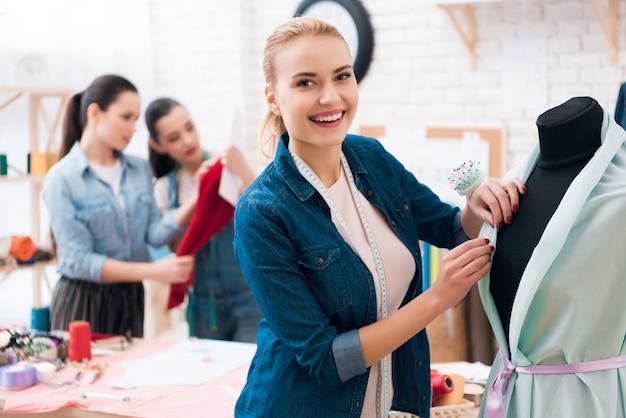 Glimlachende naaister dichtbij kleding met ledenpop