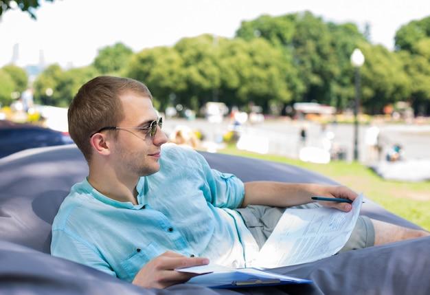 Glimlachende nadenkende jonge mens die in zonnebril op een kussen in openlucht legt, die documenten in zijn handen houdt.