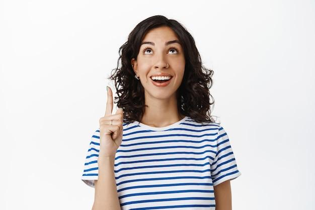 Glimlachende natuurlijke vrouw met donker krullend haar, doorboorde neus, lachend en gelukkig kijkend naar de bovenste advertentie, wijzende vinger omhoog, promotietekst op wit tonend