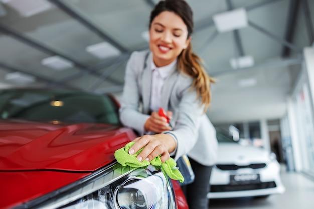 Glimlachende nette vrouwelijke autoverkoper die auto met wasmiddel en doek wrijft. alles moet glanzend en schoon zijn.
