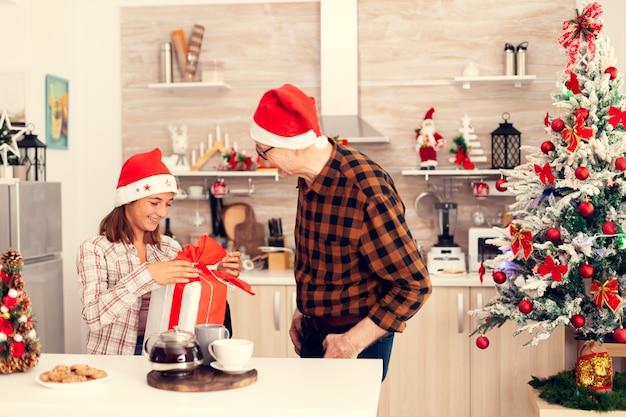 Glimlachende nicht die de doos van de kerstcadeau controleert met rode strik