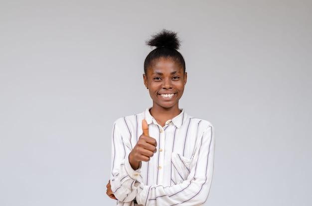 Glimlachende nigeriaanse vrouw die succes viert met duimen omhoog