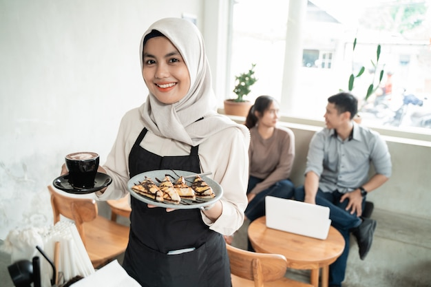 Glimlachende ober presenteert de cafébestelling van de klant