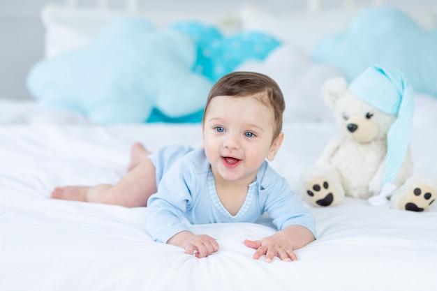 Glimlachende of lachende baby op het bed om te slapen met teddybeer, babykamer interieur, gezonde gelukkige kleine baby