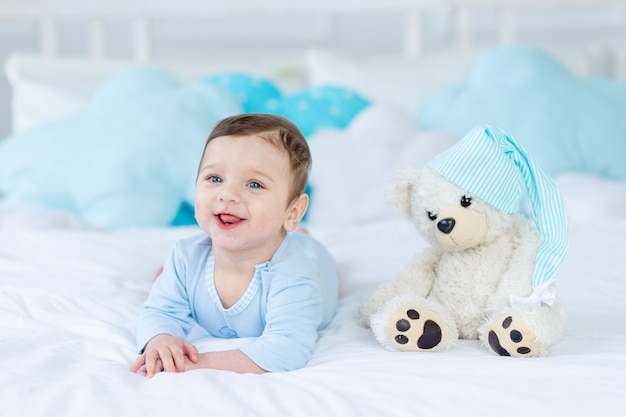 Glimlachende of lachende baby op het bed om te slapen met teddybeer, babykamerinterieur, gezonde, gelukkige kleine baby