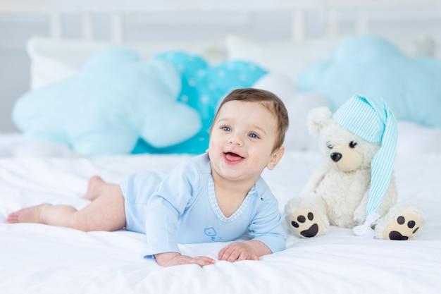 Glimlachende of lachende baby op het bed om te slapen met teddybeer, babykamerinterieur, gezonde gelukkige kleine baby