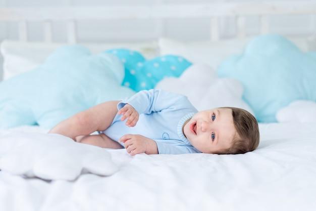 Glimlachende of lachende babyjongen op het bed om te slapen, gezonde gelukkige kleine baby in blauwe romper