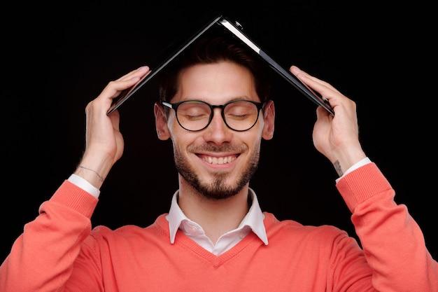 Glimlachende onbezorgde jongeman met gesloten ogen die laptop boven het hoofd houdt terwijl hij zich verbergt voor zijn werk