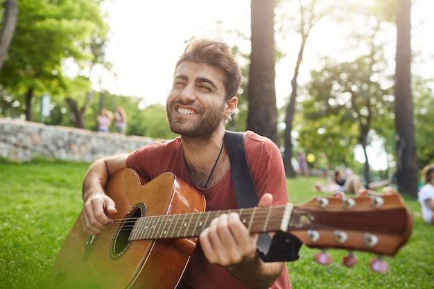 Glimlachende onbezorgde kerel die lied zingt en gitaar speelt in park