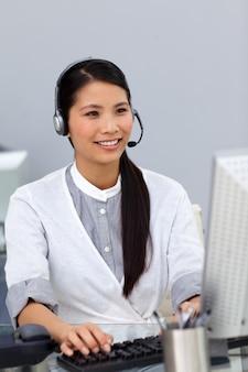 Glimlachende onderneemster die bij een computer werkt