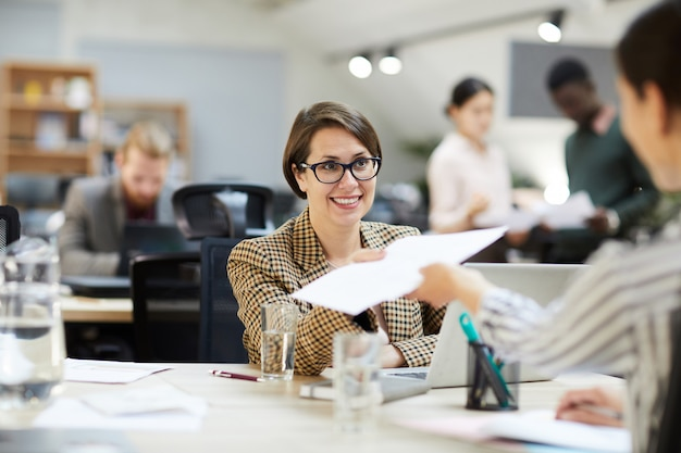Glimlachende onderneemster die documenten geeft aan collega