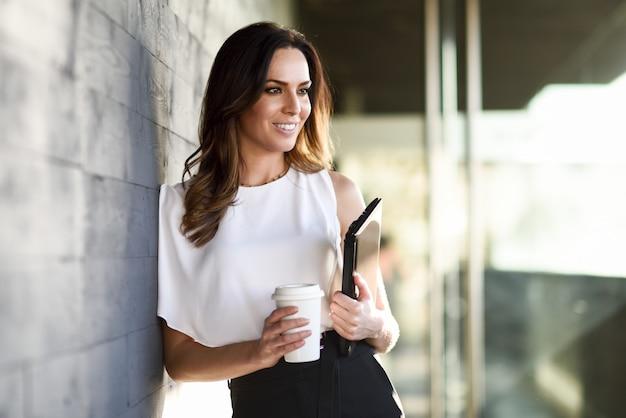 Glimlachende onderneemster die een koffiepauze in een bureaugebouw neemt.