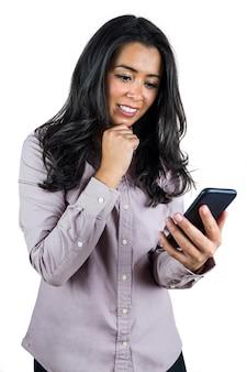 Glimlachende onderneemster die haar smartphone gebruiken tegen een witte achtergrond
