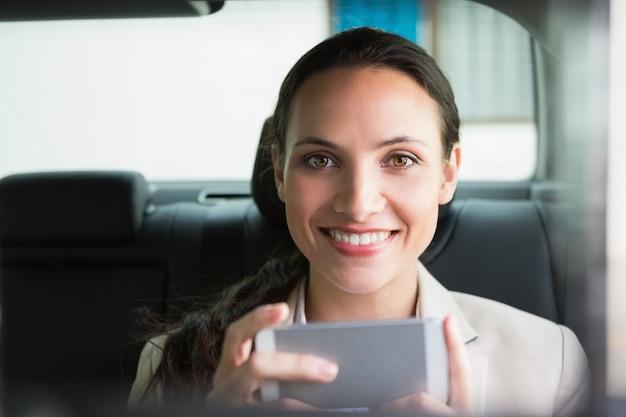 Glimlachende onderneemster die haar telefoon met behulp van