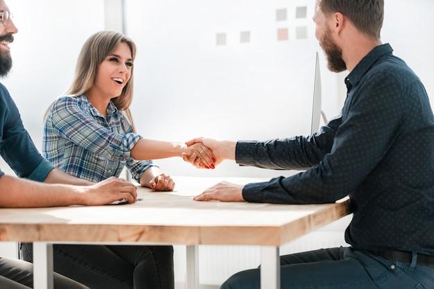 Glimlachende onderneemster die handen met haar zakenpartner schudt