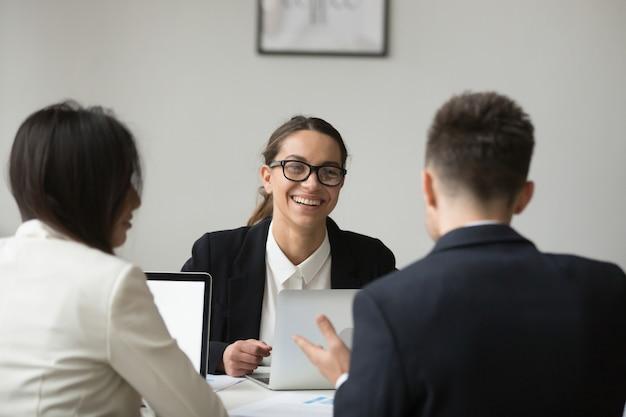 Glimlachende onderneemster die met ondergeschikt over rapporten spreekt
