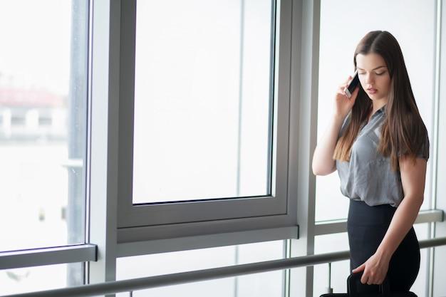 Glimlachende onderneemster die op de telefoon spreekt