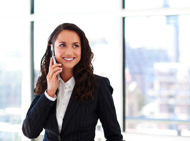 Glimlachende onderneemster die op telefoon spreekt
