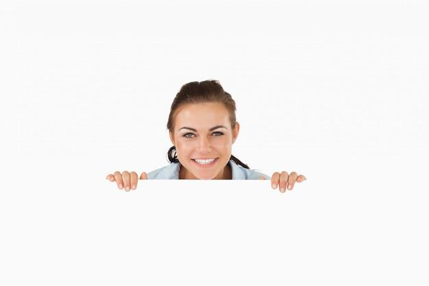 Glimlachende onderneemster die over muur kijkt