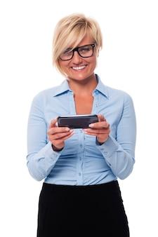 Glimlachende onderneemster die slimme telefoon en tekstberichten houdt