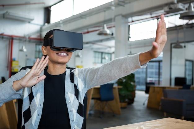 Glimlachende onderneemster die virtuele werkelijkheidshoofdtelefoon met behulp van