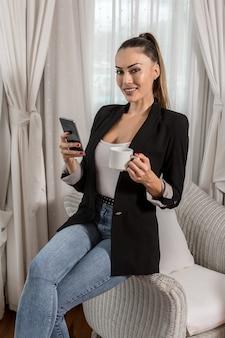 Glimlachende onderneemster gebruikend smartphone en drinkend koffie