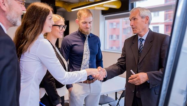 Glimlachende onderneemster het schudden hand met hogere zakenman in de raadsvergadering