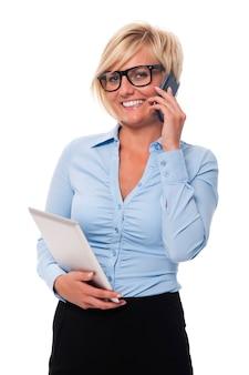 Glimlachende onderneemster met mobiele telefoon en digitale tablet