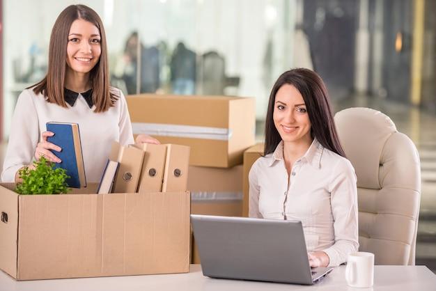 Glimlachende onderneemsters die en dozen in bureau werken inpakken.