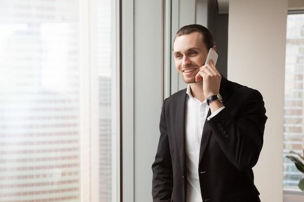 Glimlachende ondernemer beantwoordt de oproep op kantoor
