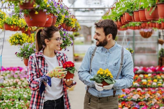 Glimlachende ondernemers staan in kas en houden potten met kleurrijke bloemen.