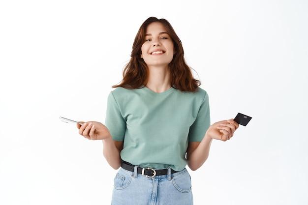 Glimlachende ontspannen vrouw die gemakkelijk betaalt met creditcard en mobiele telefoon, kijk onbezorgd naar voren met een blij gezicht na het verzenden van geld met smartphone-app, online winkelen, witte muur