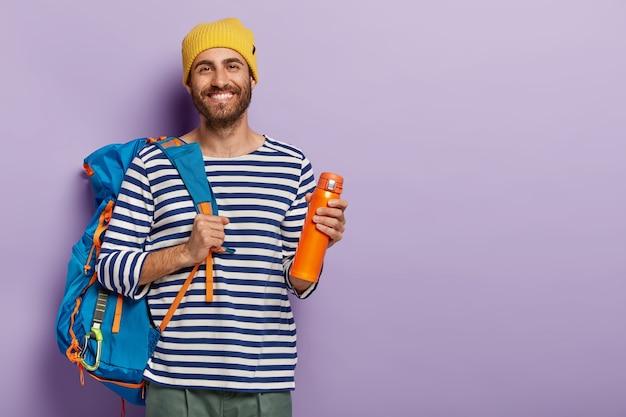 Glimlachende opgetogen mannelijke toerist heeft geweldige reis, draagt een grote rugzak, drinkt koffie uit een fles, is in een goed humeur, draagt een gele hoed