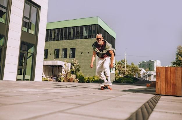 Glimlachende opgewonden man die geniet van zijn skateboardtraining