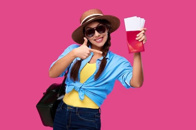 Glimlachende opgewonden reizigersvrouw die de kaartjes van het vakantievliegtuig en paspoort via vingergebaar tonen