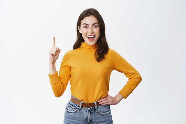 Glimlachende opgewonden vrouw die reclame toont, vinger omhoog wijst en geamuseerd naar voren staart, staande tegen een witte muur