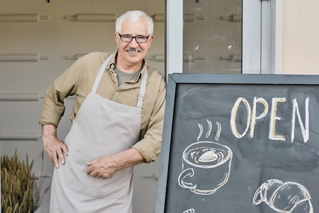 Glimlachende oude kaukasische bakker in schort en bril die aan het bord staat met getrokken gebak en drank