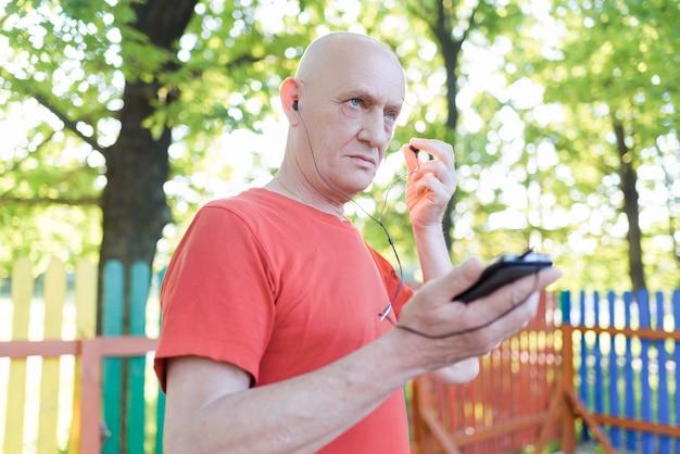 Glimlachende oude man in vrijetijdskleding en witte koptelefoon luisteren muziek van zijn smartphone in stadspark op zonnige dag.