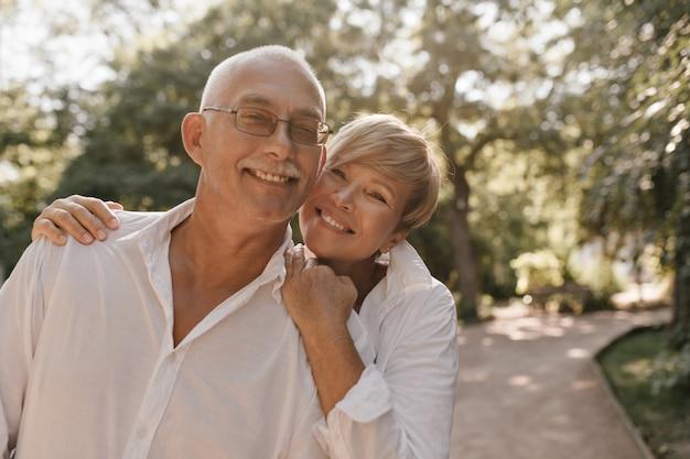 Glimlachende oude man met grijs haar en snor in glazen en licht shirt knuffelen met blonde vrouw in witte kleren in park.