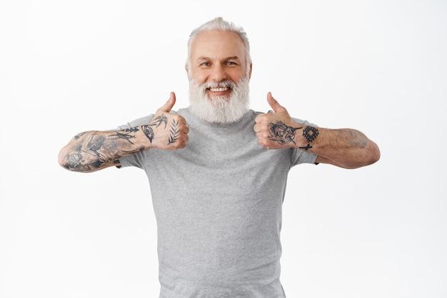 Glimlachende oude man toont duimen en ziet er gelukkig en trots uit, prijst geweldig werk, uitstekend werk, staat tevreden en blij tegen de witte muur