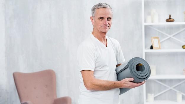 Glimlachende oude mens die zich thuis met gerolde yogamat bevindt
