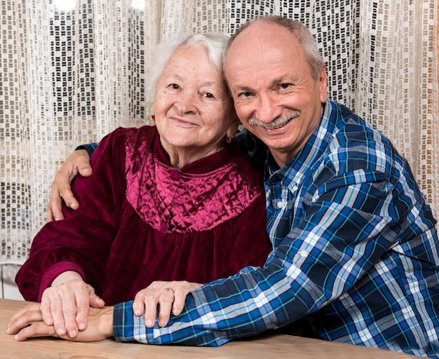 Glimlachende oude moeder met bejaarde zoon thuis