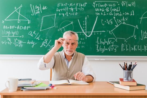 Glimlachende oude professor van wiskunde in klaslokaal