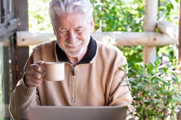Glimlachende oude senior man in wintertrui die buiten op het balkon zit te bladeren door sociale media-inhoud met een laptopcomputer met een koffiekopje in zijn hand.