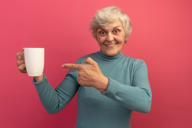 Glimlachende oude vrouw die een blauwe coltrui draagt en naar een kopje thee wijst