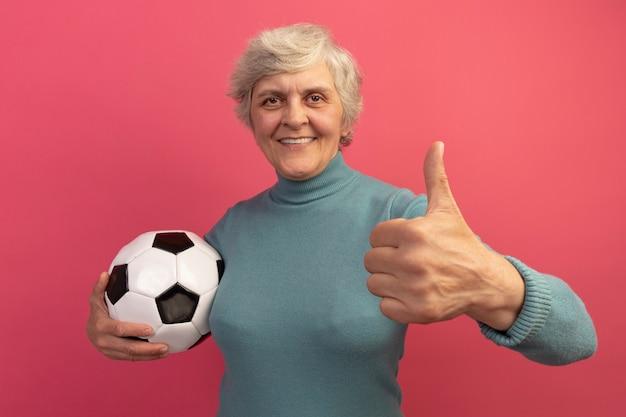 Glimlachende oude vrouw die een blauwe coltrui draagt en voetbal vasthoudt en naar de voorkant kijkt met duim omhoog geïsoleerd op roze muur