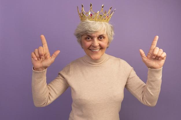 Glimlachende oude vrouw die een romige coltrui draagt en een kroon naar boven wijst
